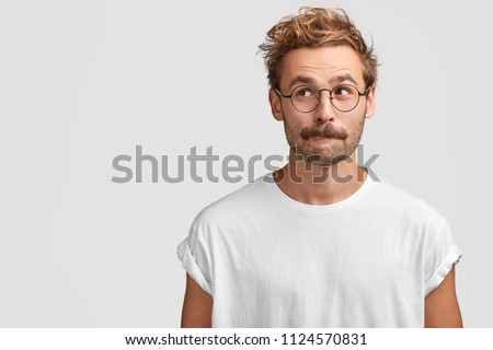 Puzzled handsome male with mustache, bites lower lip and looks curiously aside, thinks about something, dressed in casual white t shirt, stands against blank wall with copy space for your text