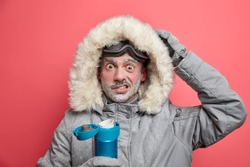 Puzzled male hiker has frozen face shocked by cold conditions in expedition wears warm jacket and ski goggles drinks hot beverage poses indoor against vivid rosy background. Lifestyle snowboarding