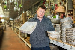 Puzzled man choosing handmade wickerwork for interior in home decor shop..