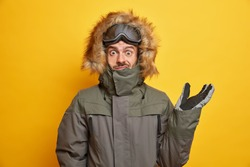 Puzzled man in winter outfit raises hand and looks confused at camera wears hood of his anorak coat goes skiing during spare time isolated over yellow background. Season clothing leisure concept