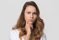 Puzzled perplexed young woman with distrustful face isolated on blank studio wall, unbelieving suspicious girl looking at camera doubtful uncertain bewildered criticize on white background portrait