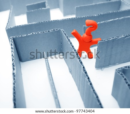 puzzled red plasticine guy with question mark on his had lost in a blue labyrinth