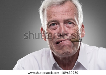 Puzzled senior man on gray background. Studio shot of puzzled senior man with cigar in his mouth