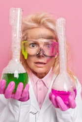 Puzzled shocked female chemist tests product samples mixes ingredients in flasks surprised with reagent reaction wears safety glasses white coat rubber gloves. Bubbles after solution distillation