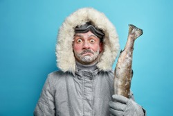 Puzzled surprised frozen man spends long hours outdoor during severe cold day dressed in grey winter jacket and gloves holds fish wears ski glasses isolated on blue background. Frosty weather