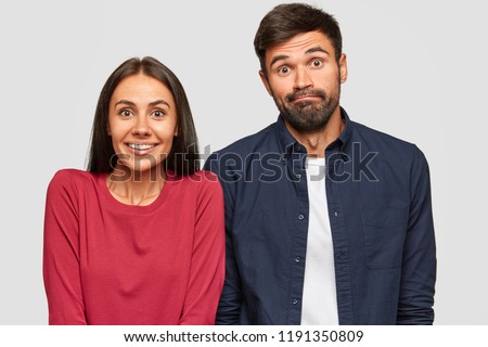 Puzzled uncertain young woman and man look with doubtful expressions at camera, try to make decision, stand against white background. Girlfriend, boyfriend express apathy ask: So what do now?