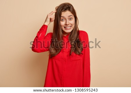 Puzzled unsure delighted young woman scratches head and looks directly at camera, makes decision, recieves good proposal, wears red shirt, poses over light beige background, uses imagination #1308595243
