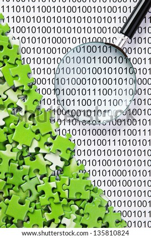 puzzles and magnifying glass on a binary code