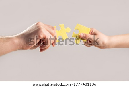 Puzzles. Hand of the child and hand of mother fold puzzle, closeup. Hands hold puzzles. Solution of problems. Mens and childs hands connecting puzzles. Hands connecting puzzle.