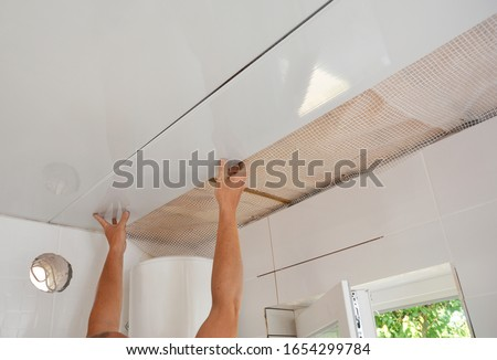 PVC Ceiling Panels, Cladding Installation. Builder installing, renovate, repair white PVC Ceiling Boards in the bathroom Stock photo ©