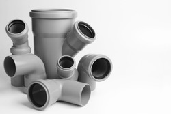 PVC plastic water pipes in gray color, insulated on a white background. The concept of installation, replacement of plastic pipes, plumbing. Copyspace.