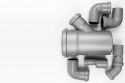PVC plastic water pipes in gray color, insulated on a white background. The concept of installation, replacement of plastic pipes, plumbing. Top view. Flatlay. Copyspace.