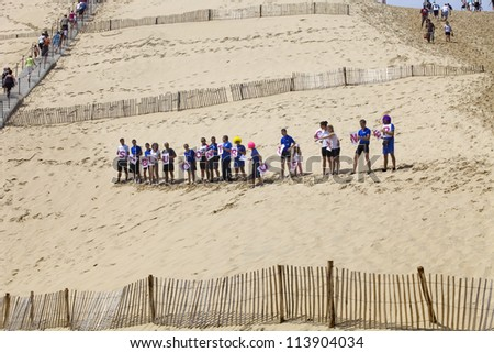 PYLA SUR MER, FRANCE - AUGUST 8: People from Siblu organization in action against cancer in the famous dune of Pyla, on August 8, 2012 in Pyla Sur Mer, France.
