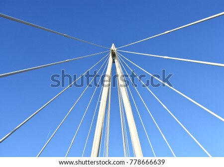 Pylon and wires of bridge with blue sky in the background. #778666639