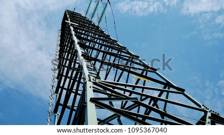 Pylon of the electric current photographed from the bottom up with clouds in the background. #1095367040