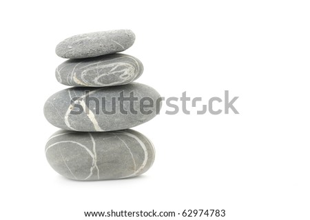 Pyramid of four striped stones over white. Soft focus