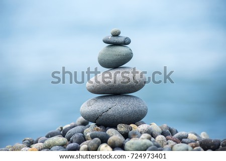 Pyramid of pebbles on the beach.Waves in background