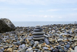 Pyramid of round stones on the seashore, the concept of harmony, balance and meditation.