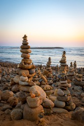 Pyramid of sea pebbles at beach on sunset, life balance and harmony concept