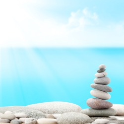 Pyramid of sea pebbles in front of water and sunny sky. Life balance and harmony concept