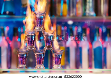 Pyramid of shot glasses with flaming cocktails #533623000