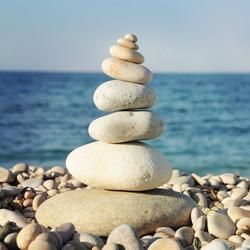 Pyramid of stones for meditation lying on sea coast