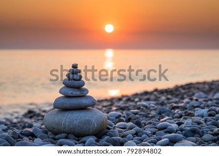 Pyramid of stones for meditation lying on sea coast at sunset #792894802