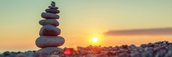 Pyramid of stones on the beach at sunset, beautiful seascape, rest and seaside vacation concept, banner panoramic view