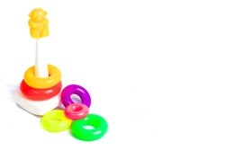 Pyramid toy build from colorful plastic rings, isolated on white background.
