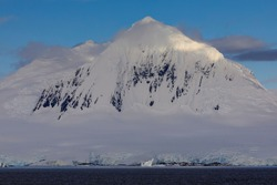 Pyramidal peak of misty Mount William in Antarctica with mist around its icy mountain summit, lit by evening light with blue sky above, in breathtaking glacial Antarctic scenery on the Antarctic coast
