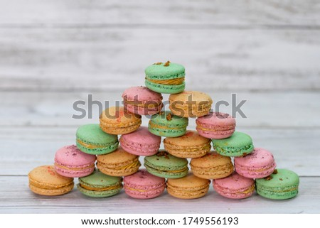 Pyramide made from macaroons of multiple flavors: pink macaroons with strawberry, green with kiwi and beige macaroons with peaches. Delicious macaroons arranged in a pyramid on a light wood background