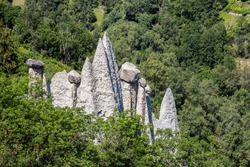 Pyramides d'Euseigne or fairy chimney rock formations in Swiss Alp. Rocks stay in balance on eroded former glacier moraine. A road pass was built under geological formation.