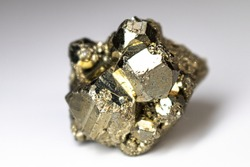 Pyrite cube up close on a neutral white background.