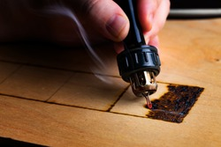 Pyrography. Wood burning with pyrography pen. Close up