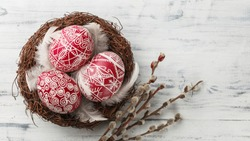 Pysanky, decorated Easter eggs in the nest, pussy willow branches and feathers on white wooden background, wide format, top view, copy space