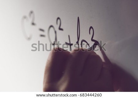 Pythagorean theorem, also known as Pythagoras's theorem, math class in the school with teacher writing mathematical formula on white board, selective focus