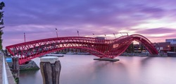 Python bridge or High Bridge in Amsterdam connectiong the Stuurmankade and Panamakade. The iron bridges is shaped like a red snake during sunset. Long exposure  - Panoramic view.