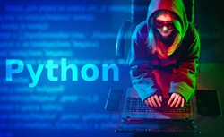 Python programming language. A long-haired girl in a hoodie writes a program in Python. Concept of programming languages. A woman develops software on Python.