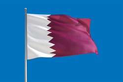Qatar national flag waving in the wind on a deep blue sky. High quality fabric. International relations concept.