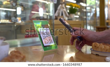 QR code cashless payment. Scan to pay system. Business or technology concept: using smartphone for scanning QR code for paying in the cafeteria