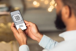 QR code on mobile phone screen, closeup. Unrecognizable african american man holding modern smartphone with bar code, paying for goods and services with payment system, creative image