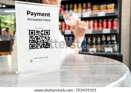 Qr code payment , online shopping , cashless technology concept. Coffee shop accepted digital pay without money , plastic tag on table. #703439101
