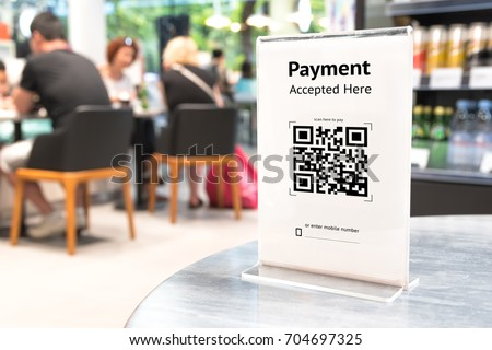 Qr code payment , online shopping , cashless technology concept. Coffee shop accepted digital pay without money , plastic tag on table. #704697325