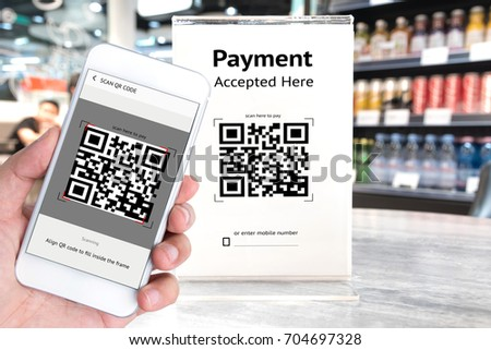 Qr code payment , online shopping , cashless technology concept. Coffee shop accepted digital pay without money , plastic tag on table and hand using mobile phone application to scan qr code. #704697328