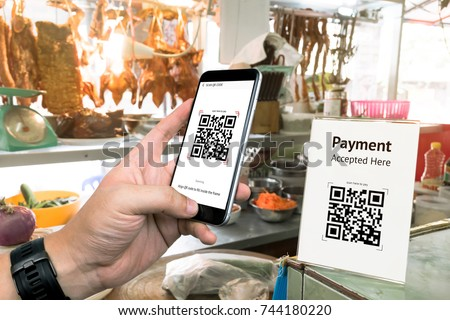 Qr code payment , online shopping , cashless technology concept. Restaurant in market accepted digital pay without money , plastic tag on table and hand using mobile phone application to scan qr code. #744180220