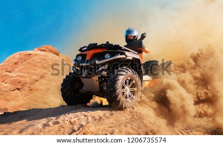 Quad bike in dust cloud, sand quarry on background