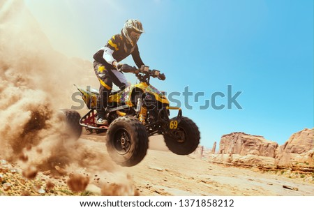 Quad bike in dust cloud, sand quarry on background. ATV Rider in the action. Stock photo ©