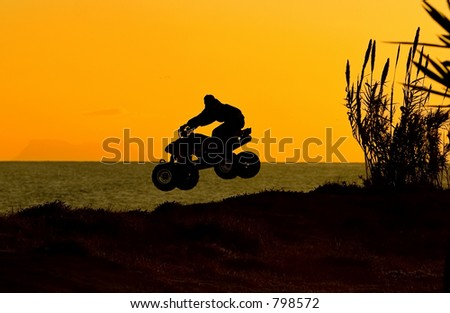 Quad bike jumping on beach at sunset in Spain on the Costa del Sol