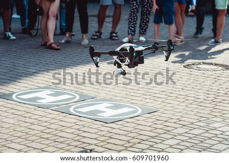 Shutterstock quad copter landing on the helicopter pad. yard paved with cobbles