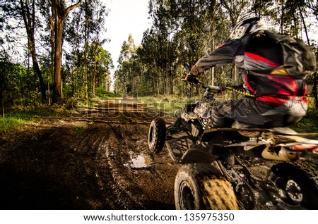 Quad rider jumping on a muddy forest trail. Stock photo ©
